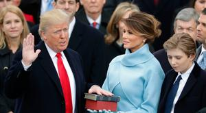 President Donald Trump takes the oath of office as his wife Melania Trump holds the bible and his son Barron Trump looks on