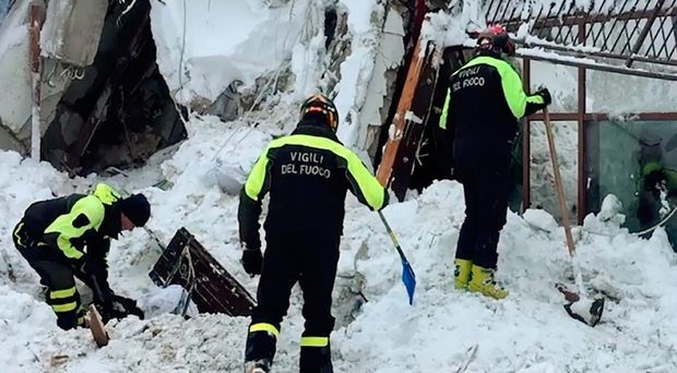 Rescuers with shovels dig through the snow in a bid to find survivors