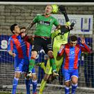 Heads up: Ards goalkeeper Aaron Hogg feels the full force of Glentoran's two-goal hero Stephen O'Flynn