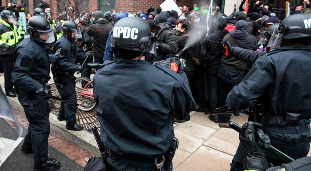 Police officers pepper spray a group of protestors
