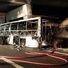 A handout photo provided by Italy's institutional agency for fire and rescue service Vigili del Fuoco on January 21, 2017 shows a firefighter extinguishing flames in the wreckage of a bus following a crash on the A4 motorway near the Verona East exit, northern Italy. AFP/Getty Images
