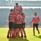 Southampton's English midfielder James Ward-Prowse celebrates with teammates after scoring the opening goal of the English Premier League football match between Southampton and Leicester City at St Mary's Stadium in Southampton, southern England on January 22, 2017. GLYN KIRK/AFP/Getty Images