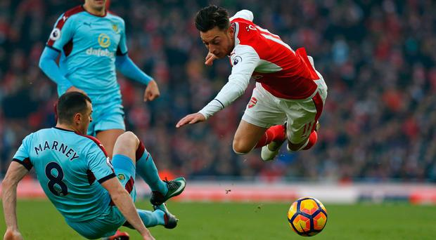 Arsenal's German midfielder Mesut Ozil (R) is tackled by Burnley's English midfielder Dean Marney during the English Premier League football match between Arsenal and Burnley at the Emirates Stadium in London on January 22, 2017. / AFP PHOTO / Ian KINGTON /