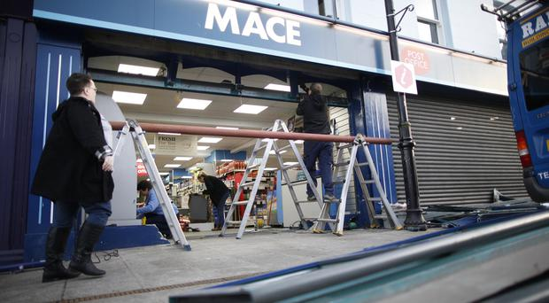 Workers begin to repair the Mace store in Randalstown following an early morning ram raid. Pic by Peter Morrison