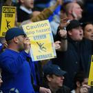 Chelsea fans hold up banners in reference to Steven Gerrard of Liverpool and his slipping over against their team last year