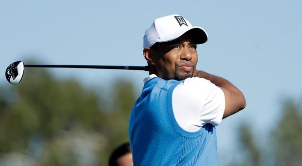 Tiger Woods watches his tee shot during the first round of the Farmers Insurance Open in San Diego
