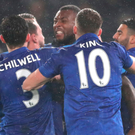 Late show: Wes Morgan is mobbed by his Leicester team-mates after scoring a late equaliser at Derby last night