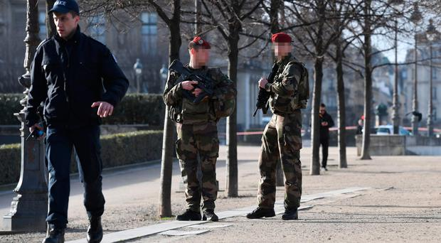 French police officers and soldiers patrol near the Louvre museum on February 3, 2017 in Paris after a soldier has shot and gravely injured a man who tried to attack him.