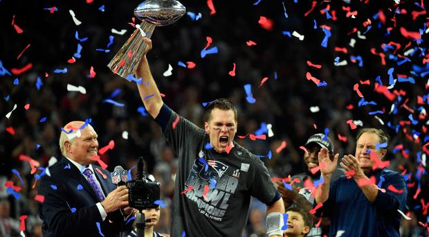 Super comeback: Tom Brady of the New England Patriots holds the Vince Lombardi trophy as head coach Bill Belichick (right) looks on after hitting back to defeat the Atlanta Falcons 34-28 in the Super Bowl