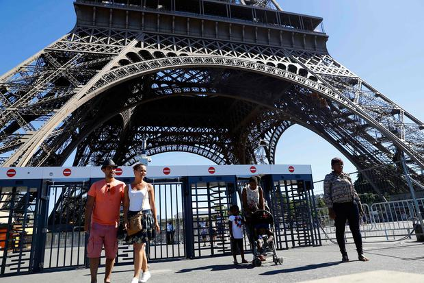 A bullet-proof glass is to be set around the Eiffel tower to protect it and secure its access. File photo taken on August 24, 2016 in Paris shows people walking past security gates at the Eiffel Tower. AFP/Getty Images