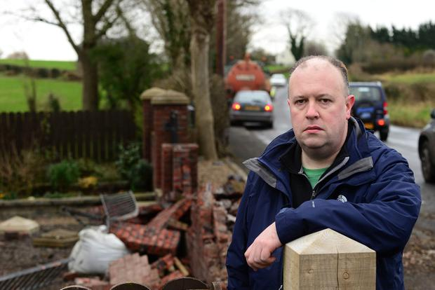 A vehicle collided with a tractor on the Belfast Road, Glenavy and then the tractor with a slurry trailer crashed into a wall of a house. Owner of the house Paul Mulvenna pictured at his home. Picture By: Arthur Allison: Pacemaker Press