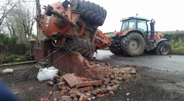A vehicle collided with a tractor on the Belfast Road, Glenavy and then the tractor with a slurry trailer crashed into a wall of a house. Picture By: Pacemaker Press