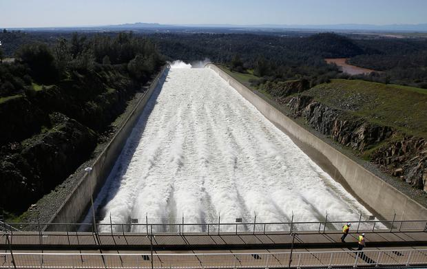 In this Saturday, Feb. 11, 2017, photo, water flows down Oroville Dam's main spillway, in Oroville, Calif. Water began flowing over the emergency spillway on Saturday for the first time in its nearly 50-year history after heavy rainfall. In addition to the emergency spillway, water also flowed through the main spillway that was significantly damaged from erosion. Officials said they'll assess the damage starting Monday. (AP Photo/Rich Pedroncelli)