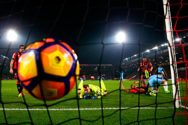 Sergio Aguero of Manchester City slides in next to Tyrone Mings of Bournemouth to score his team's second goal past Artur Boruc of Bournemouth (Photo by Michael Steele/Getty Images)