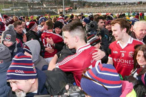 Let's celebrate: Slaughtneil players, led by Meehaul McGrath, are mobbed at Pairc Esler in Newry following their stunning victory over St Vincent's