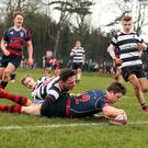 My try: Ballymena Academy's Angus Kernohan scores against Wallace High School despite the efforts of Ben Parker