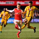 Sutton United's French striker Maxime Biamou (R) vies with Arsenal's English defender Rob Holding during the English FA Cup fifth round football match between Sutton United and Arsenal at the Borough Sports Ground, Gander Green Lane in south London on February 20, 2017. AFP/Getty Images