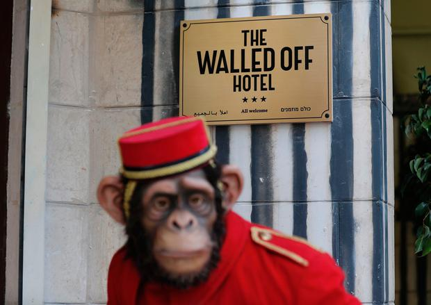 A monkey bellboy installation stands outside street artist Banksy's newly opened Walled Off hotel in the Israeli occupied West Bank town of Bethlehem, on March 3, 2017. Secretive British street artist Banksy opened a hotel next to Israels controversial separation wall in Bethlehem on Friday, his latest artwork in the Palestinian territories. / AFP PHOTO / THOMAS COEXTHOMAS COEX/AFP/Getty Images
