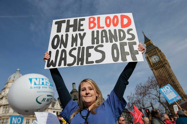 A protester, an NHS doctor, holds a placard up in front of the Elizabeth Tower, also known as Big Ben at the Houses of Parliament during a march against private companies' involvement in the National Health Service (NHS) and social care services provision and against cuts to NHS funding in central London on March 4, 2017. People gathered to demonstrate at the rally publicised by the People's Assembly Against Austerity to demand a fully and publicly funded NHS and social care service, returned fully to public ownership and provision and to say no to cuts in NHS funding. / AFP PHOTO / Daniel LEAL-OLIVASDANIEL LEAL-OLIVAS/AFP/Getty Images