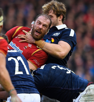 Dragon slayer: Wales' Alun Wyn Jones is tackled by Scotland's Richie Gray