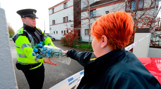 Flowers are left at the scene of an apartment fire in Dublin which claimed the lives of a woman and two children. Pic: Niall Carson/PA Wire