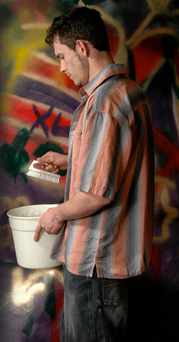 A man scrubbing graffiti off a wall. Stock image posed by model