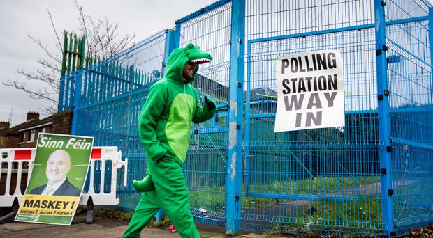 Irish language activist Dominic Sherry in a crocodile suit outside a west Belfast polling station