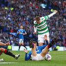 Heat of battle: Celtic's Leigh Griffiths and Rangers' Lee Wallace fight for the ball in an earlier Old Firm clash