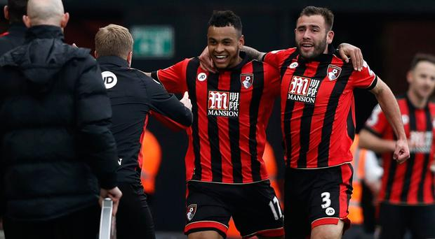 Bournemouth's Norwegian striker Joshua King (C) celebrates with Bournemouth's English defender Steve Cook (R) as he runs to Bournemouth's English manager Eddie Howe after scoring his third goal to give Bournemouth a 3-2 win in the English Premier League football match between Bournemouth and West Ham United at the Vitality Stadium in Bournemouth, southern England on March 11, 2017. Bournemouth won the game 3-2. / AFP PHOTO / Adrian DENNIS /