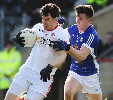 Table topper: Tyrone's Matthew Donnelly and Cavan's Dara McVeety in a tussle for the ball