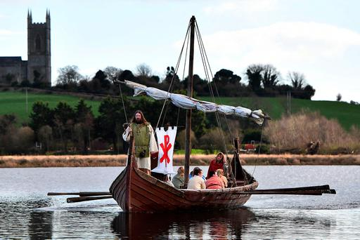 DOWNPATRICK, NORTHERN IRELAND - MARCH 12: Saint Patrick, played by Marty Burns, sails past Down Cathedral as the re-enactment of the first landing of Saint Patrick on Irish shores takes place at Inch Abbey on March 12, 2017 in Downpatrick, Northern Ireland. The Irish annals for the fifth century date Patrick's arrival in Ireland at 432 and the patron saint of Ireland's remains are believed to buried at Down Cathedral. Saint Patrick's Day itself is celebrated around the world on March 17. (Photo by Charles McQuillan/Getty Images,)