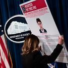 A staff member reveals a wanted poster of Igor Anatolyevich Sushchin, one of three Russians charged for in the 2014 hacking of Yahoo, during a press conference at the US Department of Justice on March 15, 2017 in Washington, DC. AFP/Getty Images