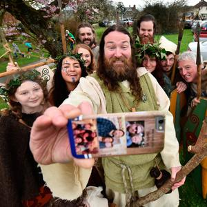 Saint Patrick, played by actor Marty Burns takes a selfie along with members of the Magnus Vikings Association before they part in the cross community Saint Patrick's Day parade on March 17, 2017 in Downpatrick, Northern Ireland. (Photo by Charles McQuillan/Getty Images)