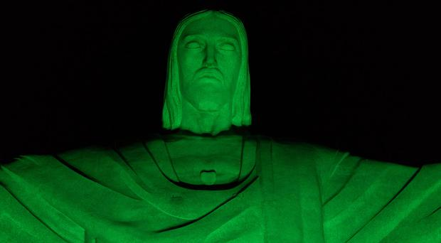 Christ the Redeemer statue is illuminated in green in honor of St. Patrick's Day in Rio de Janeiro, Brazil, Thursday, March 16, 2017. (AP Photo/Renata Brito)