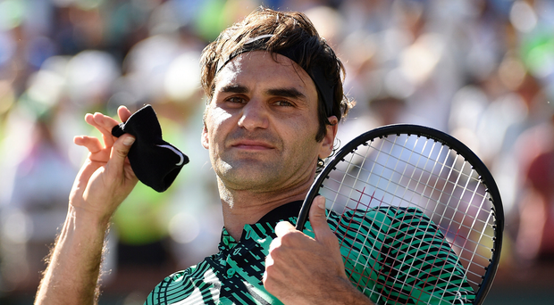 Roger Federer throws his wristband to fans in the stands as celebrates after winning the men's final in the BNP Paribas Open