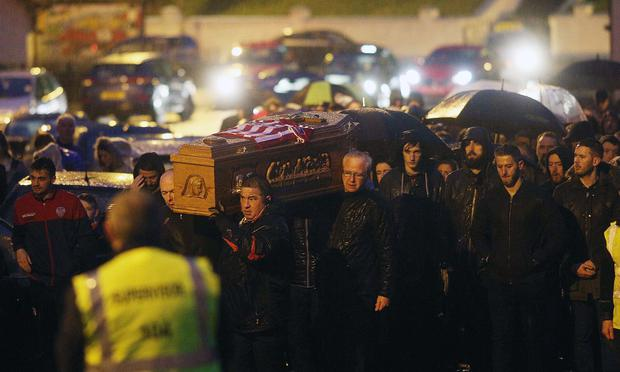The coffin of Ryan McBride is carried aloft in Londonderry last night
