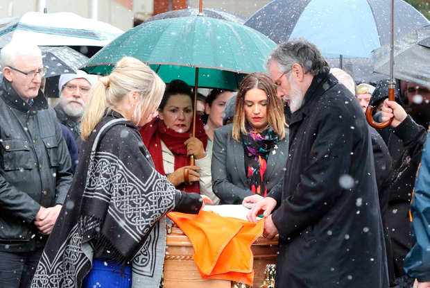 Sinn Fein president Gerry Adams (R) and Northern Sinn Fein leader Michelle O'Neill (L) lay the Irish flag on the coffin of former Northern Ireland Deputy First Minister Martin McGuinness before it is processed through the Bogside neighbourhood of Derry to his family home on March 21, 2017. AFP/Getty Images