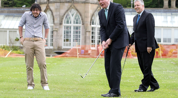 Driving force: Rory McIlroy and Peter Robinson look on as Martin McGuinness tries his hand at golf. Photo: Kelvin Boyes/Presseye