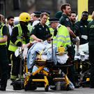 LONDON, ENGLAND - MARCH 22: A member of the public is treated by emergency services near Westminster Bridge and the Houses of Parliament on March 22, 2017 in London, England. A police officer has been stabbed near to the British Parliament and the alleged assailant shot by armed police. Scotland Yard report they have been called to an incident on Westminster Bridge where several people have been injured by a car. (Photo by Carl Court/Getty Images)