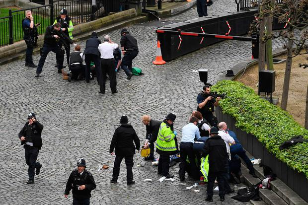 A policeman points a gun at a man on the floor at the top of the frame as emergency services attend the scene outside the Palace of Westminster, London, after a policeman was stabbed and his apparent attacker shot by officers in a major security incident at the Houses of Parliament. PA