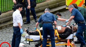 The Westminster attacker is treated by paramedics as the knives he used in his attack (ringed) lie nearby in the street. Photo: Stefan Rousseau/PA Wire