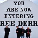 People stand underneath a Republican message painted on a wall in the Bogside area of Derry on March 22, 2017. Pic Getty