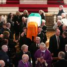 The sons of Northern Ireland's former deputy first minister and ex-IRA commander Martin McGuinness, Emmet (left) and Fiachra (right), carry his coffin out of at St Columba's Church Long Tower