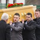 The late George Gilmore's son George Gilmore Jnr (back carrying his father's coffin)