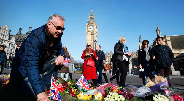 Members of the public lay tributes to those killed in the terror attack in Parliament Square in London