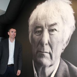 Brian McCormick beside a huge photograph of his uncle Seamus Heaney at HomePlace in Bellaghy