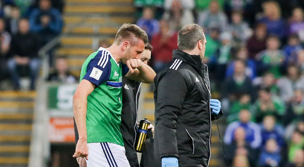 Pitch battle: Concerned looks all around for Gareth McAuley on Sunday night