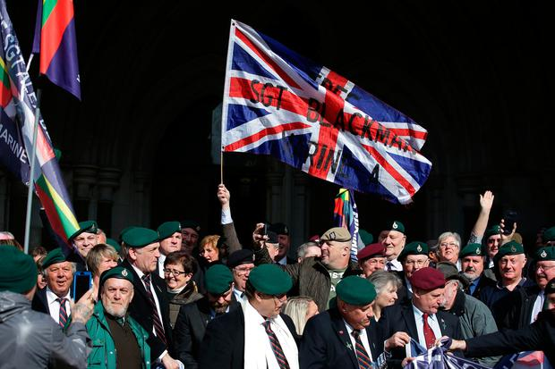 Supporters of former British soldier Alexander Blackman, Marine A, react outside the The Royal Courts of Justice in London on March 28, 2017, after learning the result of his sentence.