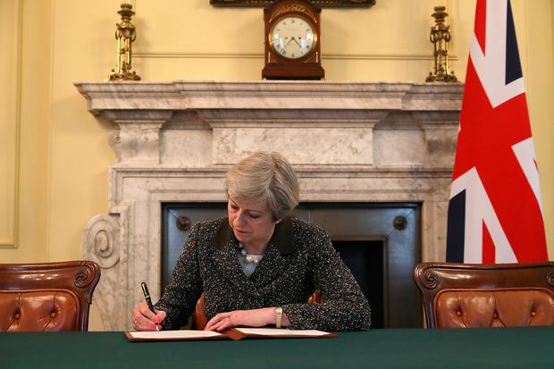 British Prime Minister Theresa May in the cabinet office signs the official letter to European Council President Donald Tusk invoking Article 50 and the United Kingdom's intention to leave the EU on March 28, 2017 in London, England. (Photo WPA Pool/Getty Images)