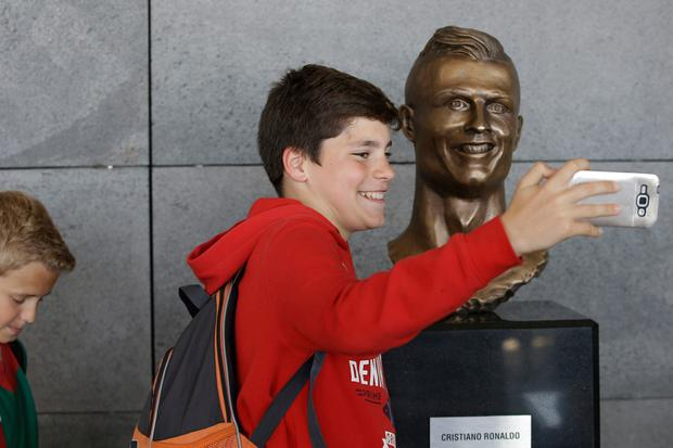 A youth takes a selfie next to the bust of Cristiano Ronaldo at the Madeira international airport outside Funchal, the capital of Madeira island, Portugal, Wednesday March 29, 2017. (AP Photo/Armando Franca)